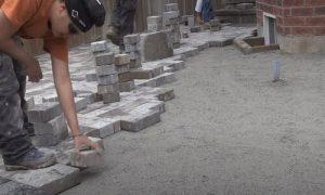 Simcoe Interlocking worker laying bricks on to residential walkway