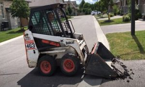 Paving Simcoe County bobcat removing the old asphalt from a home driveway