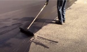 Paving Simcoe County sealcoating worker applying on parking lot
